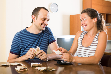 25s: Happy european woman watching her husband counting money