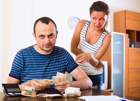 Young woman and her husband counting money for paying debts