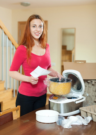 crock pot: Woman with electric crock pot in her kitchen at home