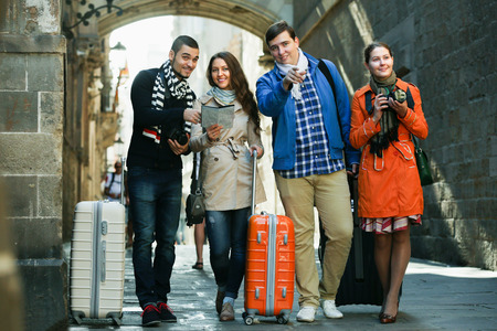 group direction: Group of smiling friends with luggage checking direction in map outdoor