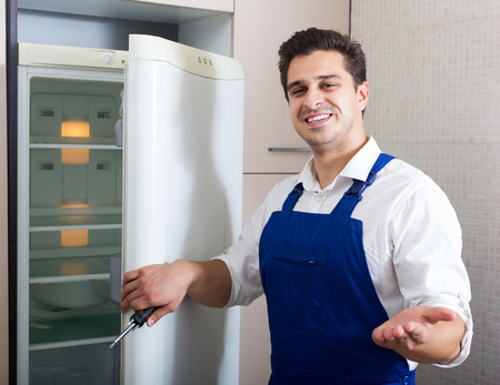 refrigerator kitchen: Happy young handyman repairing refrigerator in kitchen