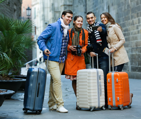 luggage: Group of positive friends shooting mutual portrait on cell phone outdoors Stock Photo