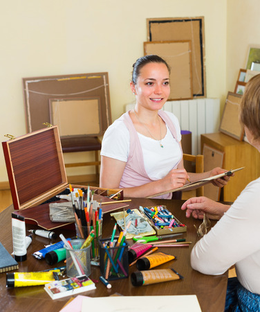 sitter: Smiling female artist painting portrait of mature woman at art studio with pencil and paints