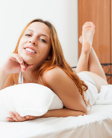 arouse: Happy red-haired woman woke up on the white sheets in the bed at home