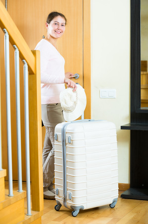 interphone: Positive young woman standing in hall with packed luggage