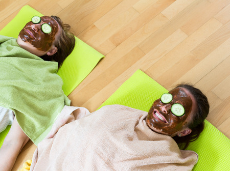 cognate: Two smiling adult females relaxing with a homemade mask for skin face Stock Photo