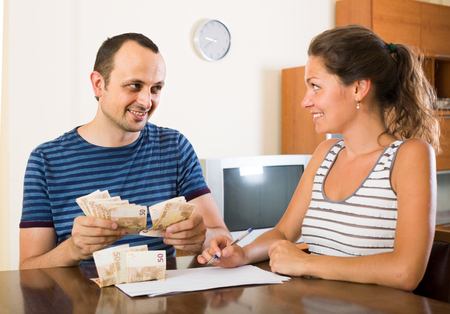 counting money: smiling spanish woman watching her husband counting money