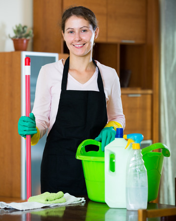 regular people: smiling maid in apron dusting and wiping in residential property