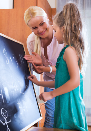 introducing: Positive blonde woman introducing numbers to small girl at home