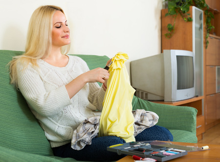mending: Attentive blond girl on couch mending cotton and smiling Stock Photo