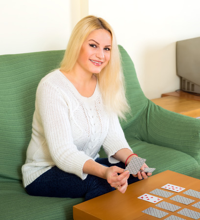 predictor: Beautiful blond woman sitting by the table at home and playing cards game Stock Photo