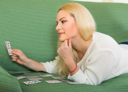predictor: Relaxed blonde girl playing solitaire on sofa in home interior Stock Photo