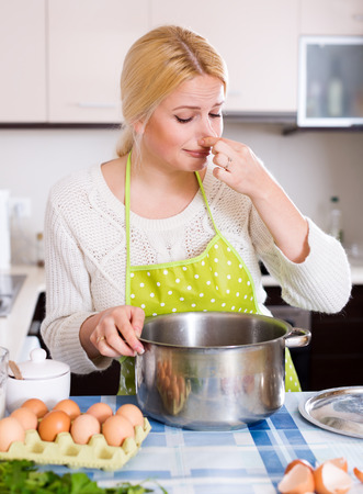 avoiding: Young housewife pinched her nose avoiding bad smell from pan