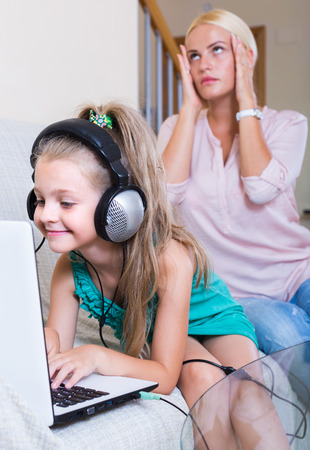 internet porn: Young mother displeased her little daughter playing  too much computer game Stock Photo