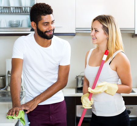 dusting: Black man with cheerful white woman dusting in domestic kitchen