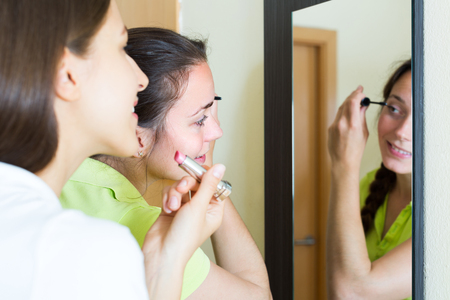 makeups: Smiling girls doing make-up in front of the mirror at home