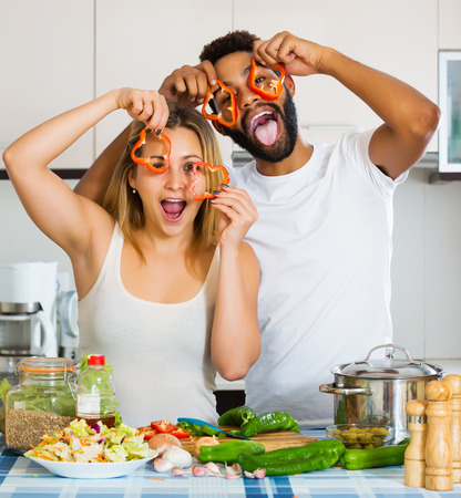 interracial couple: Portrait of happy interracial couple cooking vegetables and laughing