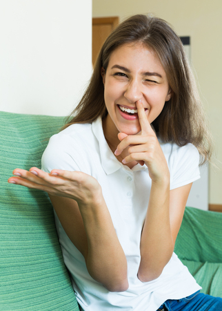 drollery: Laughing girl sitting on the couch with the finger in the nose