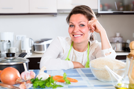 householder: Portrait of smiling woman in green apron sitting by the table in a kitchen