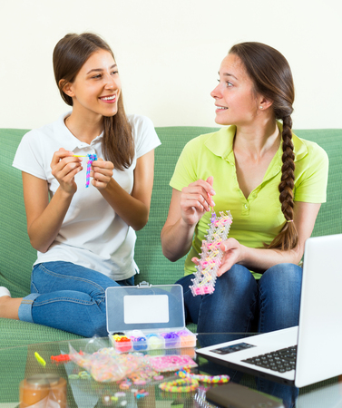 avocation: Cheerful girls at home are making handmade accessories from rubber bands