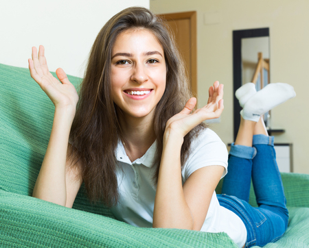 woman on couch: Portrait of cheerful long-haired teenager girl lying on the couch at home