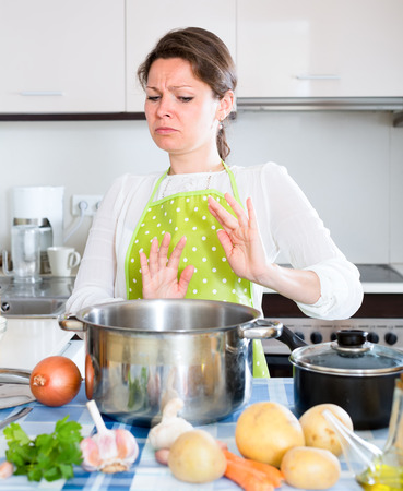 foxy girls: Young beautiful housewife looking with disgust at a pan with spoiled smelly food inside it Stock Photo