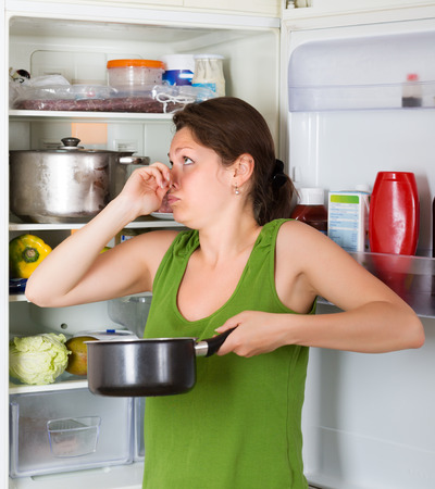 frowy: Brunette girl holding her nose because of bad smell from food near refrigerator  at home