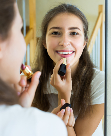 finger on lips: Happy young teenager applying lipstick in front of a mirror at home