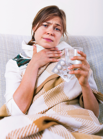 tonsillitis: Young woman having heavy sickly tonsillitis in domestic interior Stock Photo