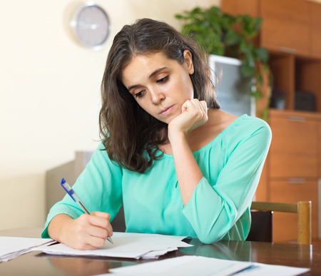parsimony: Stressed woman reading  documents at home