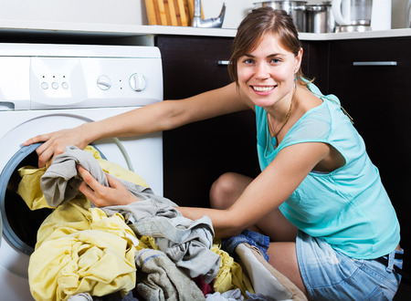 Smiling woman enjoying clean clothes without stains after laundry