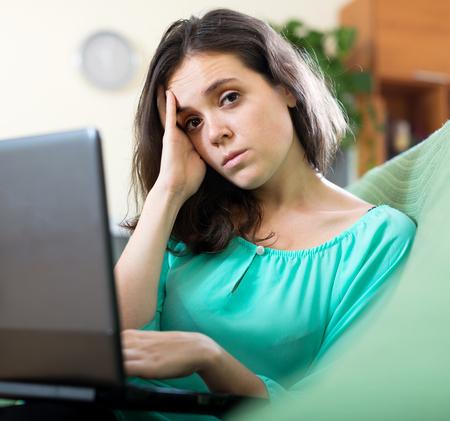 ennui: Sad  woman  using  laptop in living room