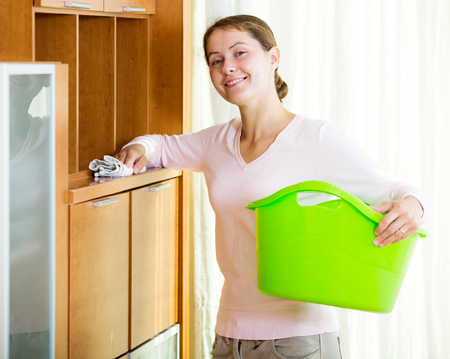 dusting: Portrait adult woman dusting furniture at home and smiling