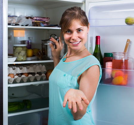 householder: Positive adult girl arranging space of fridge shelves indoors Stock Photo