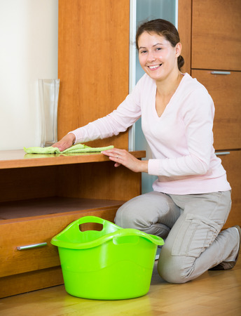 spanish woman: Cheerful spanish woman cleaning at home with smile on face Stock Photo