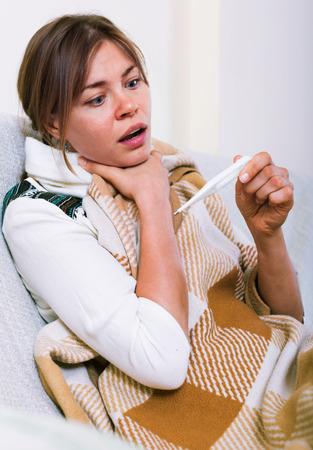 Unhappy woman having heavy sickly tonsillitis in domestic interior