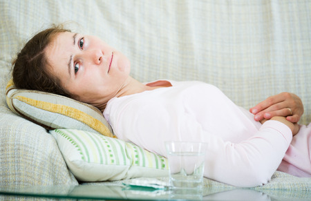 early pregnancy: Portrait of adult spanish girl folding up with belly pain indoor Stock Photo
