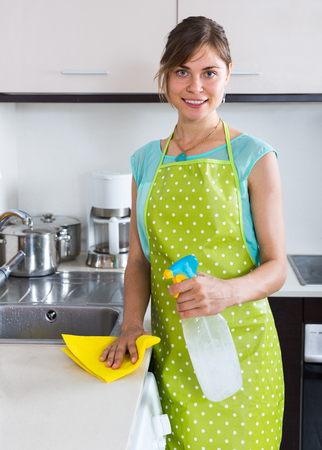 cleanup: smiling maid doing professional clean-up in home kitchen