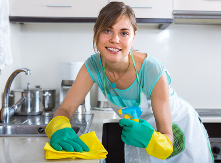 cleanup: spanish maid doing professional clean-up in home kitchen Stock Photo