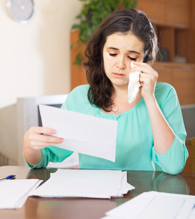 poorness: One woman in depression reads unpleasant letter and crying