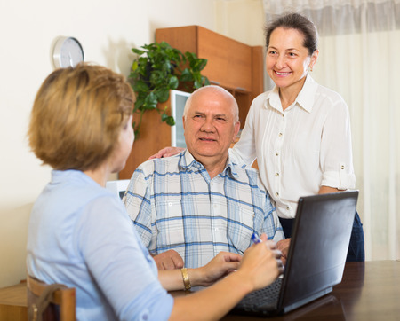 census: Senior smiling couple answer questions of social worker at home. Focus on man