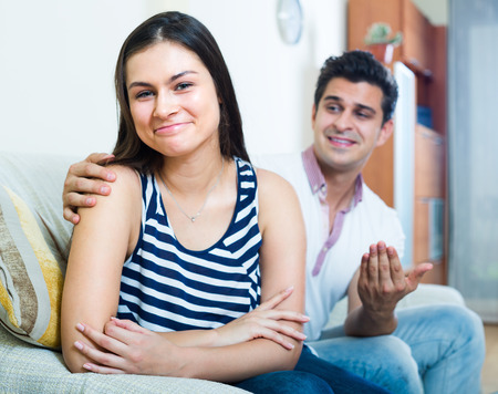 Portrait of young woman and man making efforts to reconcile with her at home