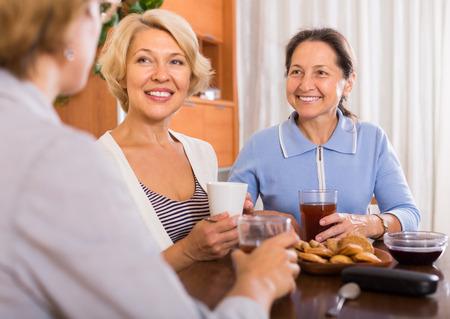 woman sit: Three mature women drinking tea with cookies indoor. Focus on brunette Stock Photo