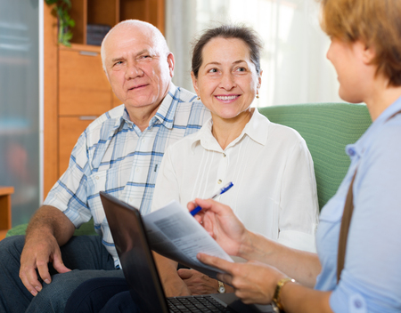 retirement homes: Mature american couple filling questionnaire for employee with laptop of the bank Stock Photo