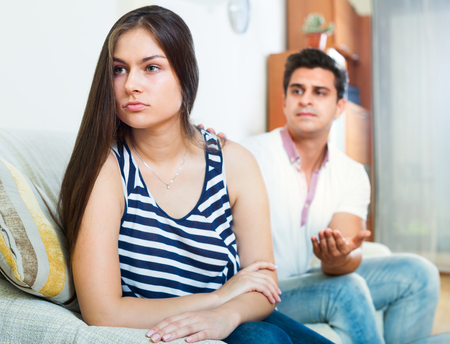 spite: Angry young spouses having domestic argue in the living room Stock Photo