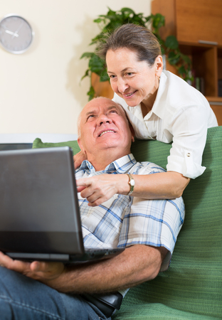 russian man: Happy elderly russian  man and mature woman using laptop at home