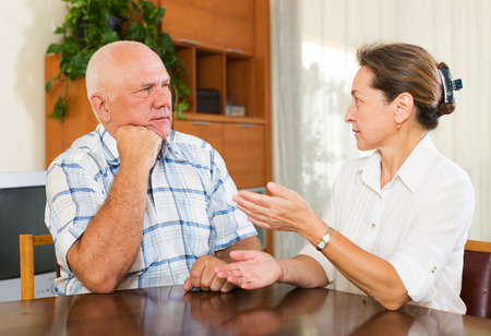 calm woman: Serious elderly couple talking in home interior