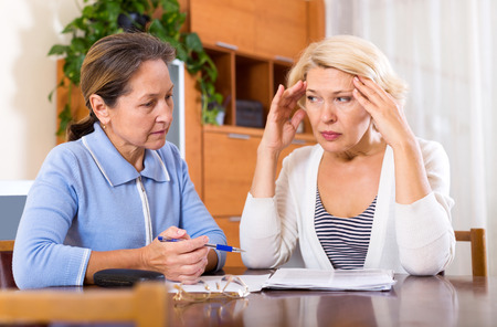 women friends: Depressed female pensioners discussing finances indoor. Focus on the left woman Stock Photo