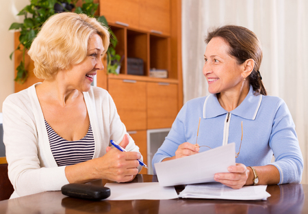 mature woman sitting: Happy mature ladies signing documents at home and looking at each other.Focus on the woman on the left Stock Photo