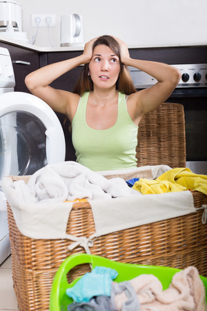 unsound: Unhappy young woman cheking white clothes near washing machine  indoors